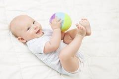 Juego Toy Ball, niño feliz del bebé que miente en la parte posterior que juega los juguetes suaves imagenes de archivo