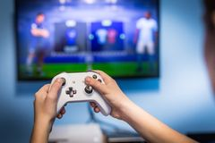 Juego video del juego y del juego en el juego-cojín de la tenencia del videojugador de la diversión de la TV y la consola video d fotos de archivo libres de regalías