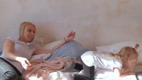Juego y salto rubios atractivos jovenes de la mamá en la cama con su hija encantadora almacen de metraje de vídeo