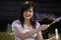 Juegos adolescentes de la muchacha con la varita de la burbuja Fotos de archivo libres de regalías