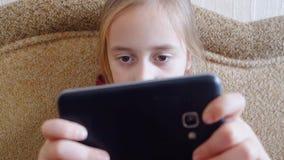 Juegos adolescentes de la muchacha en el teléfono mientras que se sienta en el sofá metrajes