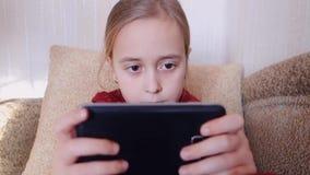 Juegos adolescentes de la muchacha en el teléfono mientras que se sienta en el sofá almacen de video