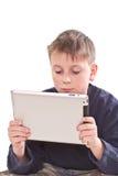 Juegos adolescentes en el ordenador de la tablilla Foto de archivo libre de regalías