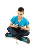 Juegos adolescentes en las palancas de mando que se sientan en el suelo Imágenes de archivo libres de regalías