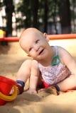 Juegos adorables del bebé en una salvadera Imágenes de archivo libres de regalías