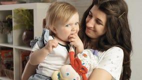 Juegos bastante caucásicos con la trapo-muñeca que se sienta en los brazos en su cámara lenta de la mamá joven almacen de video