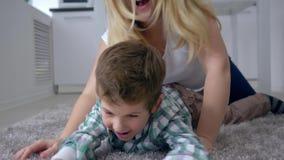 Juegos con la comida, madre alegre con la lucha del hijo para comer en la placa que miente en el primer del piso almacen de video