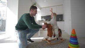 Juegos con los niños, padre feliz que juega con el hijo lindo en el asiento del caballo de la felpa y que balancea en casa en coc almacen de metraje de vídeo