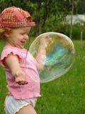 Juegos de cinco años de la muchacha con la burbuja de jabón Foto de archivo libre de regalías