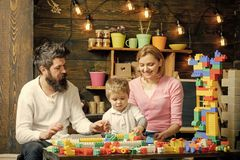 Juegos de la familia El padre, la madre y el hijo lindo juegan con los ladrillos del constructor La familia en caras ocupadas pas fotos de archivo libres de regalías
