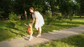 Juegos de la mamá con su pequeña hija en parque del verano Bebé de los primeros pasos con la mamá La mamá y el niño están en la t metrajes