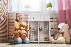 Juegos de la muchacha con la casa de muñecas fotografía de archivo