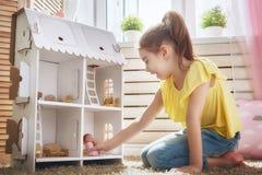 Juegos de la muchacha con la casa de muñecas imagen de archivo