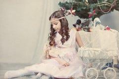 Juegos de la muchacha con la muñeca alrededor del árbol de navidad Fotografía de archivo libre de regalías
