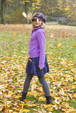 Juegos de la muchacha con las hojas de otoño Fotos de archivo libres de regalías