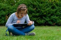 Juegos de la muchacha en la tableta en jardín Foto de archivo libre de regalías