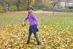 Juegos de la niña con las hojas de otoño Imágenes de archivo libres de regalías