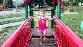 Juegos de la niña en el patio Pequeña muchacha en marco que sube Muchacha en barras de mono metrajes