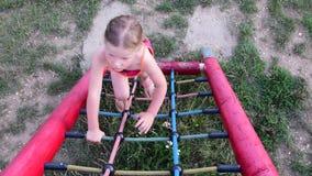 Juegos de la niña en el patio Pequeña muchacha en marco que sube Muchacha en barras de mono almacen de video