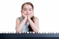 Juegos de la niña en el piano eléctrico. Foto de archivo