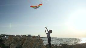 Juegos de los deportes de los niños control del muchacho del niño que vuela cometas coloridas el cielo del paisaje marino se nubl almacen de video
