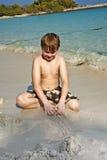 Juegos de los muchachos en la playa con la arena Fotos de archivo