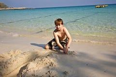 Juegos de los muchachos en la playa con la arena Imagenes de archivo