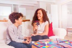 Juegos de naipe de la muchacha con su hermano menor Foto de archivo libre de regalías