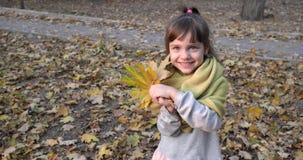 Juegos de niños atractivos con la hoja del amarillo del arce en bufanda caliente en el aire abierto en cierre del otoño para arri almacen de metraje de vídeo