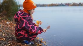 Juegos de niños con las hojas de otoño cerca del agua metrajes