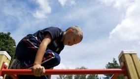 Juegos de niños en el patio en las barras desiguales contra el cielo en la cámara lenta metrajes