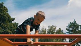 Juegos de niños en el patio en las barras desiguales contra el cielo en la cámara lenta almacen de video