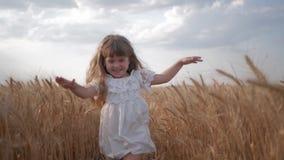 Juegos de niños en la naturaleza, niño de risa emocional en los funcionamientos blancos de la ropa con los brazos separados al en almacen de metraje de vídeo