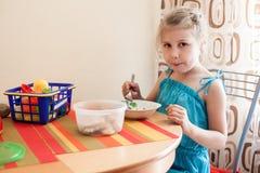 Juegos de niños jovenes con los juguetes en la tabla y la consumición Imagen de archivo libre de regalías
