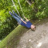 Juegos de niños jovenes en el oscilación en el patio al aire libre Imagenes de archivo