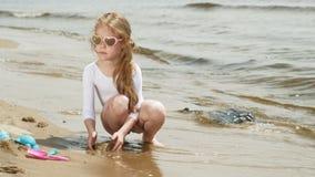 Juegos de niños de la muchacha con la arena en la playa usando las estatuillas de los moldes D?a de verano asoleado Vacaciones almacen de metraje de vídeo