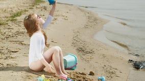 Juegos de niños de la muchacha con la arena en la playa usando las estatuillas de los moldes D?a de verano asoleado Vacaciones metrajes