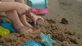 Juegos de niños de la muchacha con la arena en la playa usando las estatuillas de los moldes D?a de verano asoleado Vacaciones almacen de video