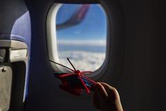 Juegos de ni?os con un helic?ptero del juguete en un avi?n contra la perspectiva de un cielo hermoso visto a trav?s la ventana foto de archivo libre de regalías