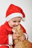 Juegos de niños del niño de la Navidad con un gato Imágenes de archivo libres de regalías