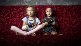 Juegos de ordenador: un muchacho y una muchacha juegan una videoconsola en la oscuridad y llevan a cabo gamepads en sus manos fotografía de archivo libre de regalías