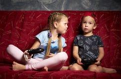 Juegos de ordenador: un muchacho y una muchacha juegan una videoconsola en la oscuridad y llevan a cabo gamepads en sus manos foto de archivo libre de regalías