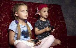 Juegos de ordenador: un muchacho y una muchacha juegan una videoconsola en la oscuridad y llevan a cabo gamepads en sus manos imagen de archivo libre de regalías