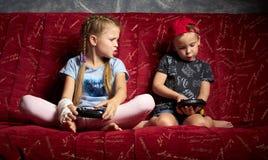 Juegos de ordenador: un muchacho y una muchacha juegan una videoconsola en la oscuridad y llevan a cabo gamepads en sus manos imágenes de archivo libres de regalías