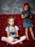 Juegos de ordenador: un muchacho y una muchacha juegan una videoconsola en la oscuridad y llevan a cabo gamepads en sus manos imagenes de archivo