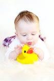 Juegos del bebé con el anadón de goma Foto de archivo
