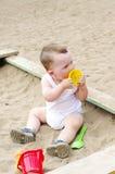 Juegos del bebé con el molde de la arena en patio Imagen de archivo libre de regalías