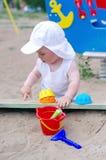 Juegos del bebé con la arena en patio Imágenes de archivo libres de regalías