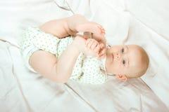 Juegos del bebé con sus piernas Fotos de archivo