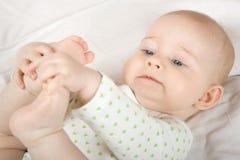 Juegos del bebé con sus piernas Fotografía de archivo libre de regalías
